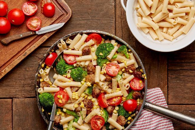 Smakowity makaron z białą kiełbasą, brokułami i pomidorami